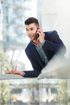 Annoyed business man talking on mobile phone