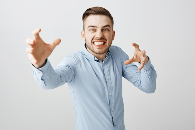 Annoyed businessman look angry reaching hands forward to strangle someone