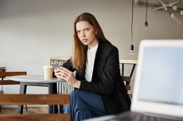 La donna di affari infastidita si siede nella caffetteria con il telefono cellulare e guardando la persona arrabbiata
