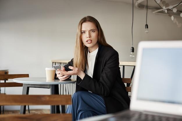 La donna di affari infastidita si siede nella caffetteria con il telefono cellulare e guardando la persona irritata