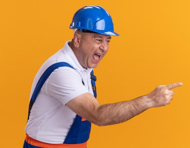 Uomo adulto caucasico infastidito del costruttore negli sguardi e nei punti uniformi a lato sull'arancio