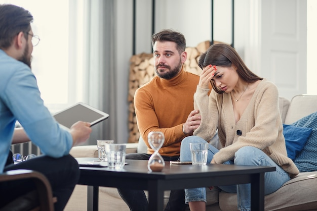 Annoyed caucasian couple of man and woman having conversation with psychologist on therapy session in light room.