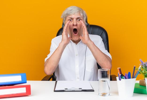 Operatore di call center femminile caucasico infastidito sulle cuffie seduto alla scrivania con strumenti da ufficio tenendo le mani vicino alla bocca chiamando qualcuno isolato sul muro arancione
