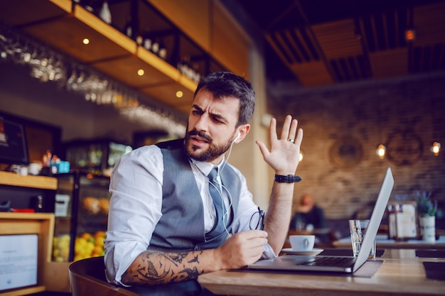 Annoyed caucasian good-looking bearded businessman in suit having argument with employee over laptop.