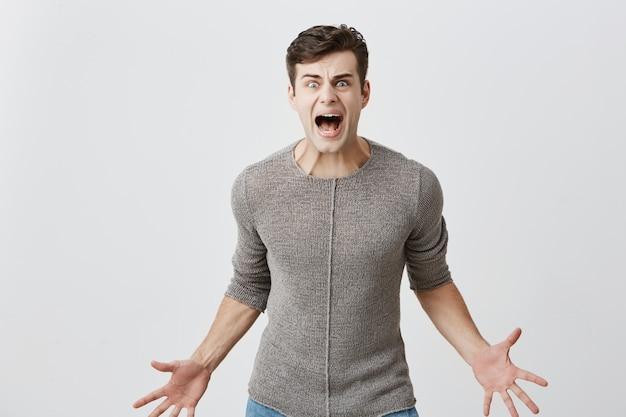 腹が立つ白人男性は猛烈なジェスチャーで手をつないで、妻と喧嘩しているように大声で叫び、屋内で家族関係を整理します。猛烈な怒りの男性が叫び、否定的な感情を表しています。