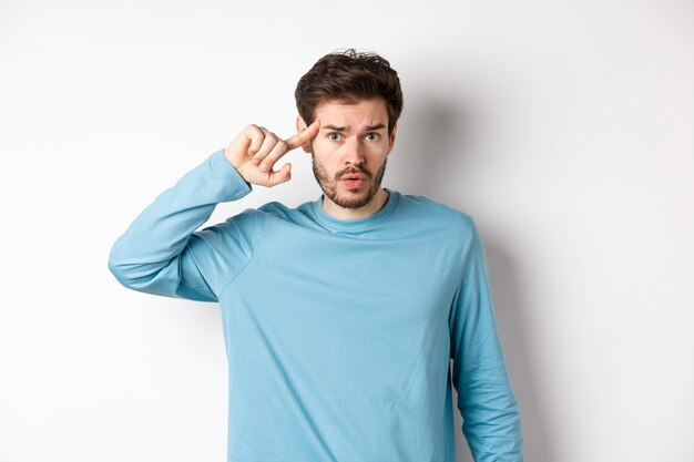 Annoyed caucasian man roll finger on temple, are you stupid or crazy gesture, scolding someone acting strange, standing in sweatshirt over white background.
