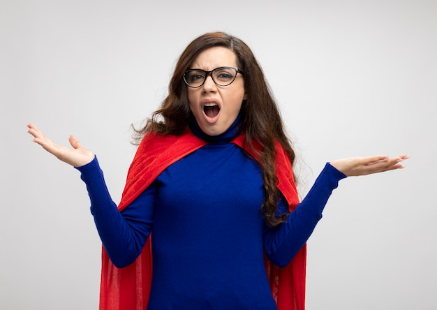 Annoyed caucasian superhero girl with red cape in optical glasses holds hands open on white