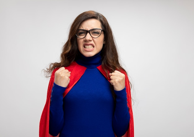Annoyed caucasian superhero girl with red cape in optical glasses keeping fists on white