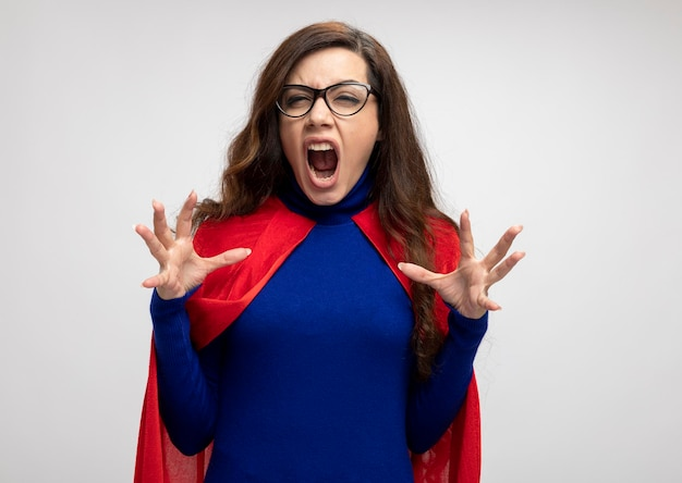 Annoyed caucasian superhero girl with red cape in optical glasses stands with raised hands on white