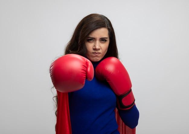 Ragazza indoeuropea infastidita del supereroe con mantello rosso che indossa guanti da boxe che fingono di pugno isolato sulla parete bianca con lo spazio della copia