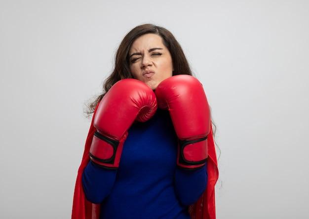 Ragazza indoeuropea infastidita del supereroe con mantello rosso che indossa i guantoni da boxe in piedi nel rack isolato sul muro bianco con lo spazio della copia
