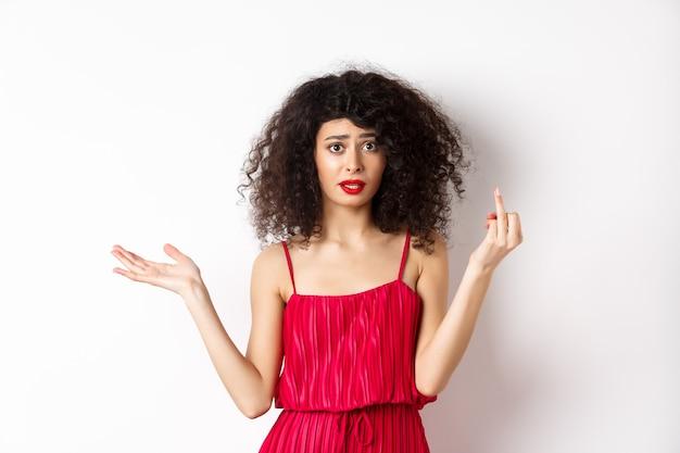 결혼 반지없이 손가락을 보여주는 빨간 드레스에 짜증이 백인 여자, 결혼에 대해 논쟁, 흰색 바탕에 화난 서.