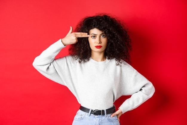 곱슬 머리를 가진 화가 백인 여자, 머리에 손 총 기호를 보여주는, 그녀의 마음을 날려 버리고, 붉은 벽에 귀찮게 서서
