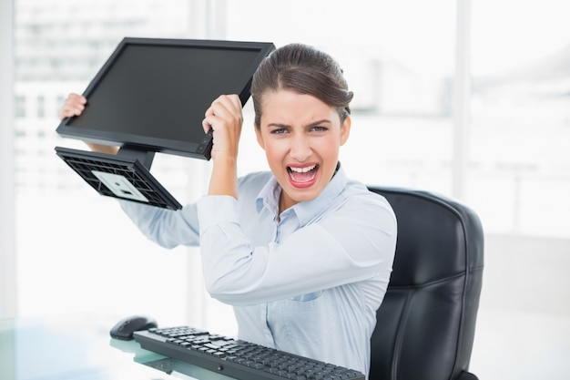 Annoyed classy brown haired businesswoman throwing her computer screen