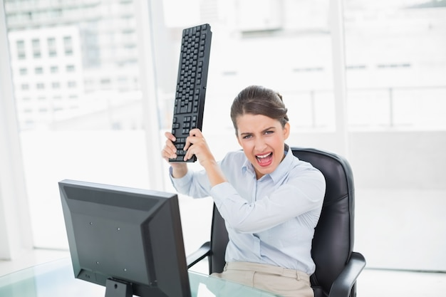 Annoyed classy brown haired businesswoman throwing her keyboard on her computer