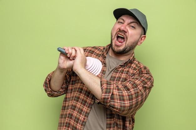 Uomo delle pulizie infastidito che tiene uno stantuffo di gomma sul petto