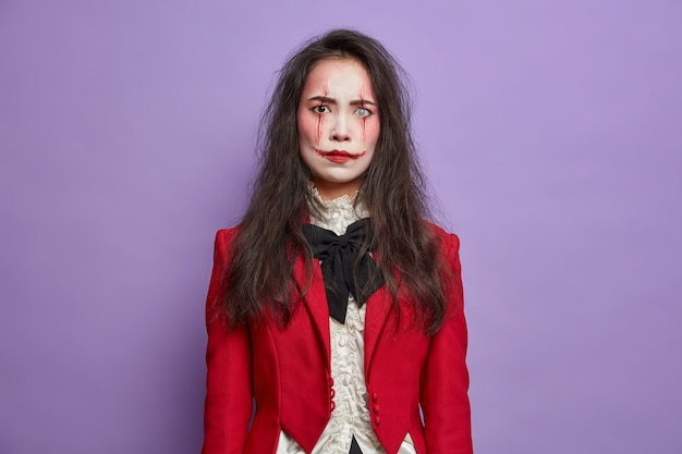La donna bruna dispiaciuta infastidita ha l'immagine del mostro spaventoso celebra il festival di ottobre e halloween indossa pose professionali di trucco spettrale contro il muro viola