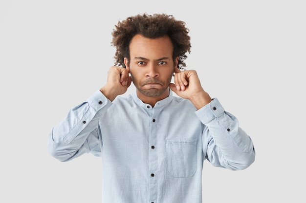 Annoyed displeased man student presses lips, covering his ears
