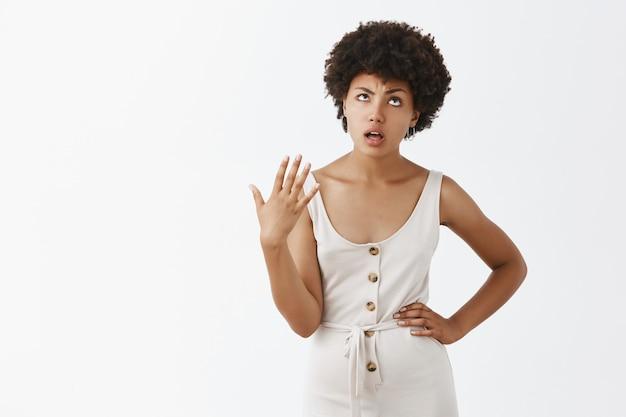 Ragazza alla moda infastidita e scontenta che posa contro il muro bianco