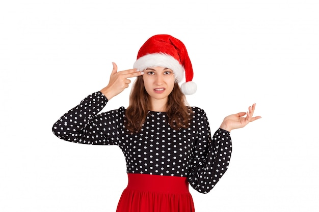 Annoyed and displeased woman in dress shrugging and holding fingers on temple. emotional girl in santa claus christmas hat isolated on white . holiday