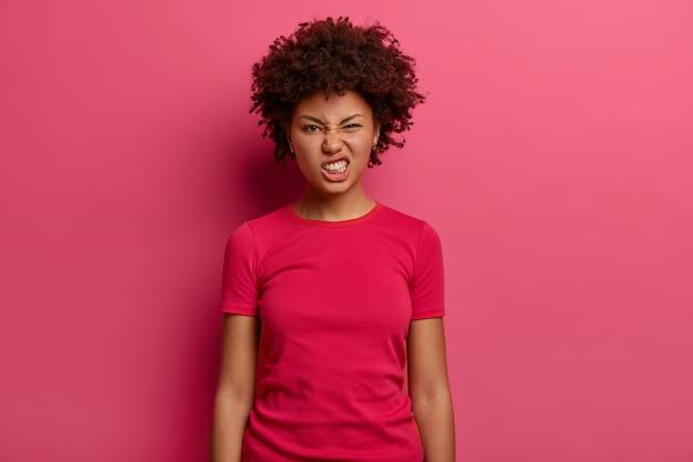 짜증이 난 불만족 여성은 이빨을 움켜 쥐고 짜증을 내고, 불쾌한 표정을 짓고, 캐주얼 티셔츠를 입고 실내에서 분홍색 벽에 포즈를 취합니다. 부정적인 얼굴 표현 개념