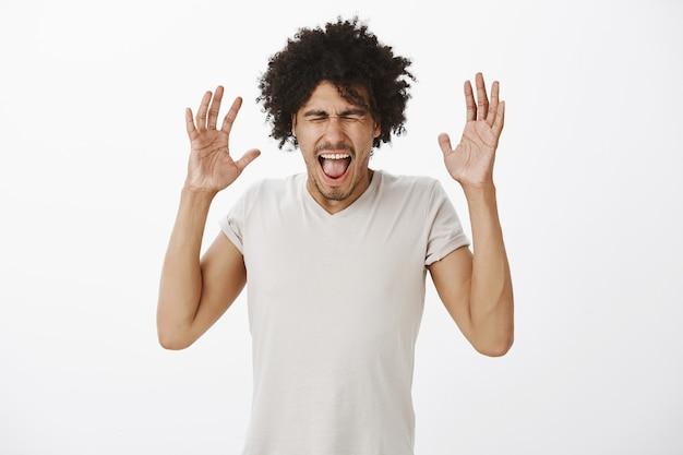 Uomo dalla carnagione scura infastidito e angosciato alzando le mani e urlando