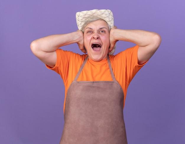 Annoyed elderly female gardener wearing gardening hat closes ears with hands