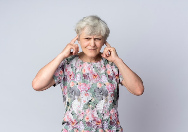 Annoyed elderly woman closes ears with fingers isolated on white wall