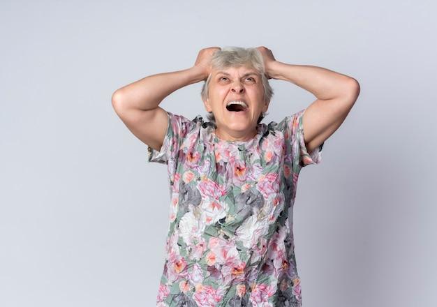 짜증이 노인 여성 보유 및 흰색 벽에 고립 된 찾고 머리를 리프트