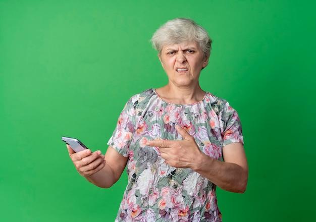 짜증이 노인 여성 보유 및 녹색 벽에 고립 된 전화 포인트