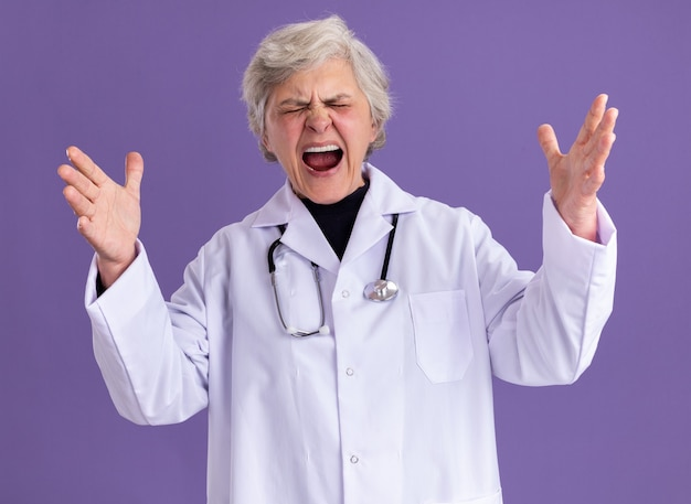 Раздраженная пожилая женщина в униформе врача со стетоскопом стоит с закрытыми глазами, взявшись за руки