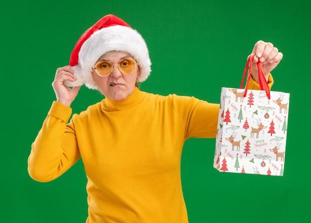 Раздраженная пожилая женщина в солнцезащитных очках в шляпе санта-клауса, держащая бумажный подарочный пакет на зеленом фоне с копией пространства