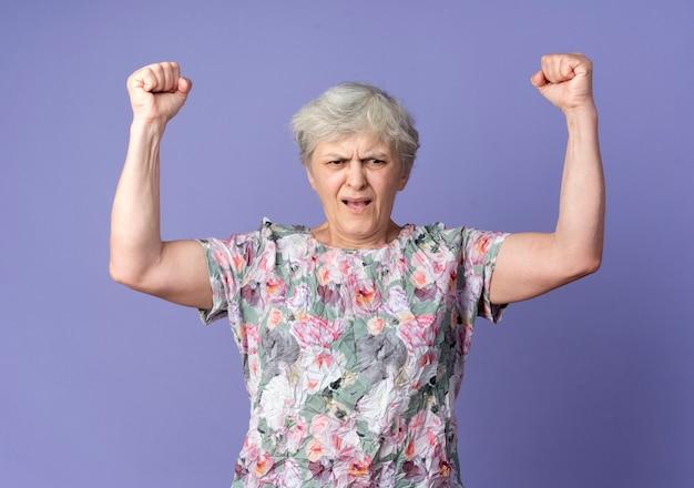 イライラする年配の女性が紫色の壁に隔離された側を見て拳を上げる