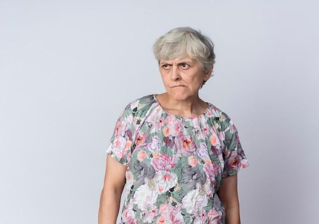 흰색 벽에 고립 된 측면을보고 짜증이 노인 여성 스탠드