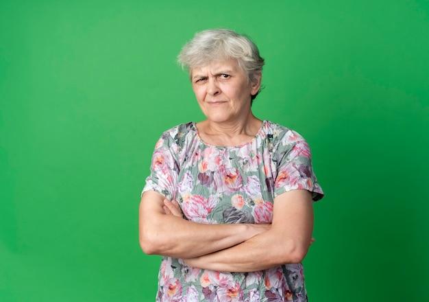 화가 노인 여성 녹색 벽에 고립 된 교차 팔 스탠드