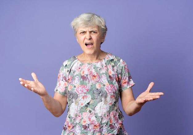 짜증이 노인 여성은 보라색 벽에 고립 된 오픈 손으로 서