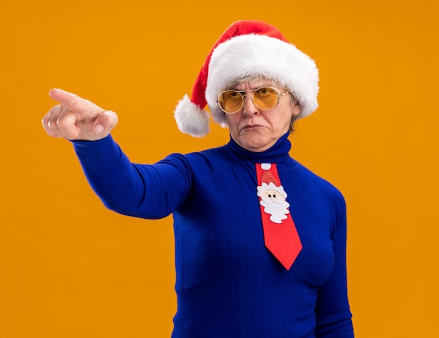 Annoyed elderly woman in sun glasses with santa hat and santa tie looking and pointing at side isolated on orange background with copy space