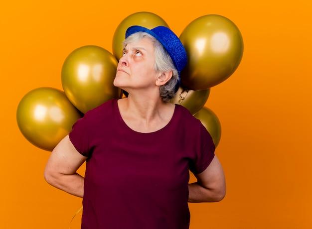 파티 모자를 쓰고 짜증이 노인 여성이 오렌지를 바라 보는 뒤에 헬륨 풍선을 보유하고 있습니다.
