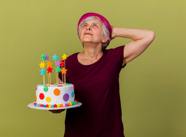 Annoyed elderly woman wearing party hat puts hand on head behind holding birthday cake isolated on olive green wall with copy space