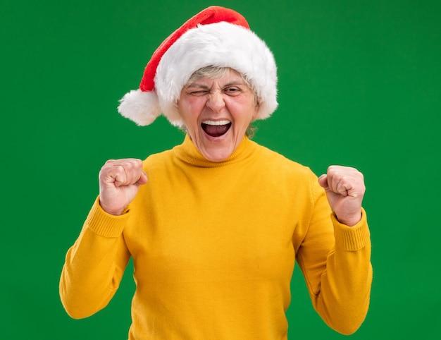 주먹을 유지하는 산타 모자와 짜증이 노인 여성 무료 사진
