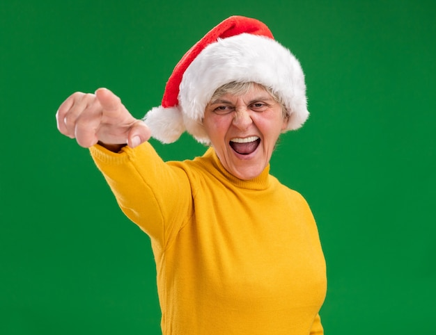 Annoyed elderly woman with santa hat looking and pointing at camera isolated on purple background with copy space