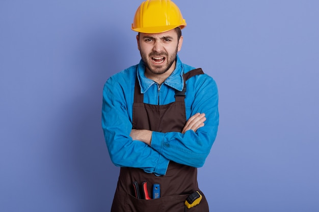 Annoyed emotional workman wearing yellow protective construction helmet, has much work to do, scream with stress and panic, keeps arms folded.