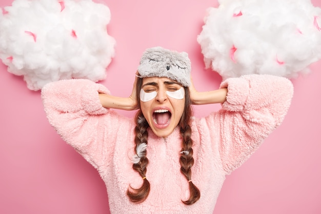Annoyed emotional young woman cannot fall asleep because of terrible noise covers ears and exclaims from anger keeps mouth opened wears blindfold pajama poses indoor