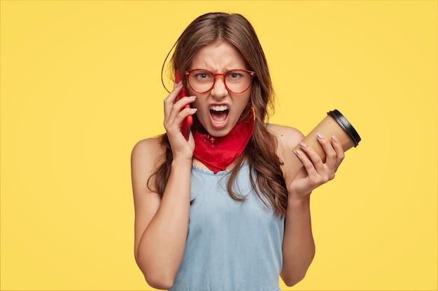 La donna europea infastidita urla con sentimenti negativi mentre ha una conversazione telefonica, sostiene porta il caffè in una tazza usa e getta
