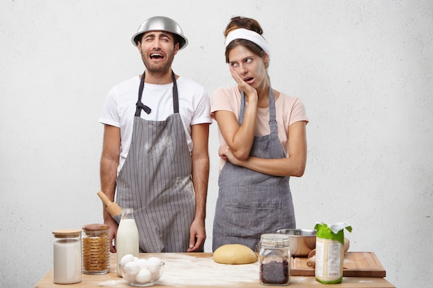 Donna infastidita in grembiule irritata dal marito che si lamenta in cucina