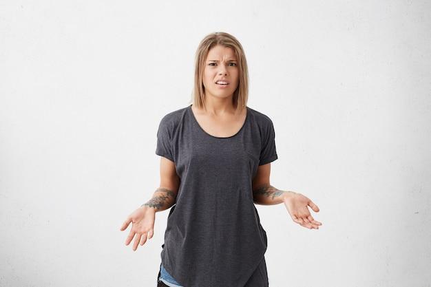 짧은 염색 머리를하고 헐렁한 회색 티셔츠를 입고 성가신 찡그린 얼굴을하는 여성이 손에 문신을 한 채로 불확실성과 혼란을 겪고 있습니다. 흰 벽에 포즈 화가 여성