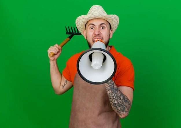 ガーデニングの帽子をかぶっているイライラした庭師の男は熊手を保持し、スピーカーを探して大声で叫ぶ