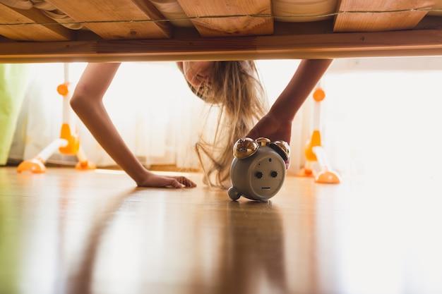 早朝にベッドの下で目覚まし時計に手を伸ばすイライラした女の子