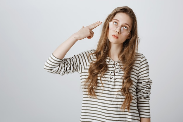 Annoyed girl roll eyes and shooting herself fake gun gesture, going nuts