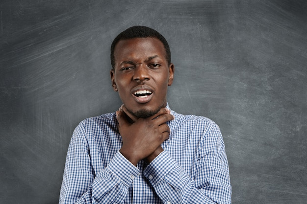 Annoyed grumpy young african teacher or student in casual shirt holding himself for neck, making suicide gesture, as if trying to drown or choke himself, showing his irritated and fed-up attitude